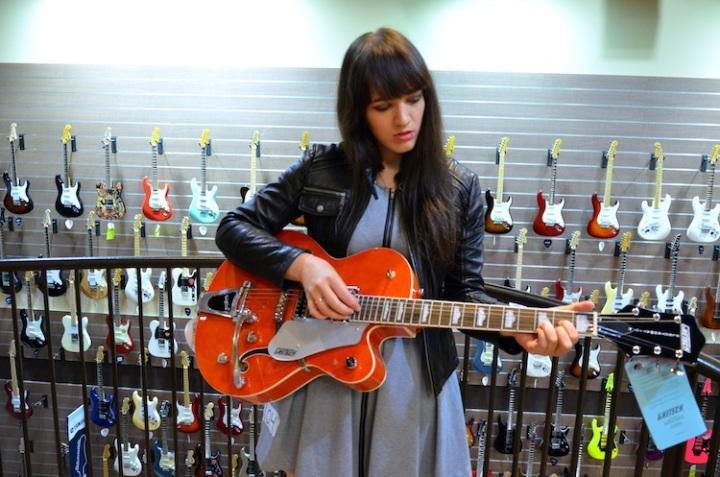 Sage playing orange guitar