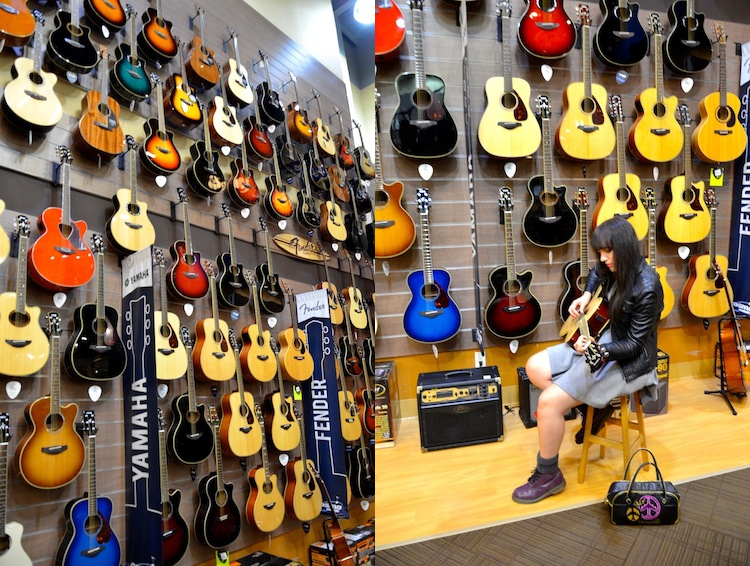 sage playing guitar in front of a wall of guitars